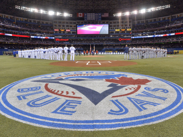 Toronto Blue Jays and Cleveland Indians stand on the base lines before the start of their opening day AL baseball game in Toronto on Tuesday, April 2, 2013. THE CANADIAN PRESS/Nathan Denette